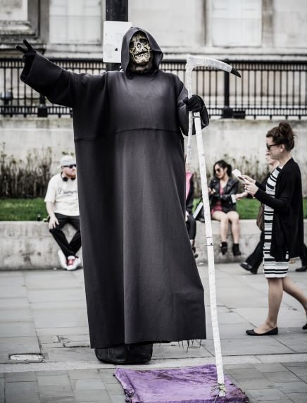 A man costumed as the grim reaper: with a skull-like mask, dark hooded robe, and a large stylized scythe.